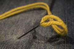Close up, yellow needle and thread on jeans cloth royalty free stock photo
