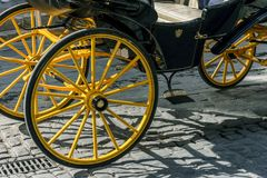 Detail of yellow wheel of horse carriage on a cobblestone street Royalty Free Stock Image