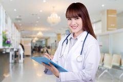 Detail of a young Asian woman doctor holding a clipboard standing on hospital background. health care concept stock photos