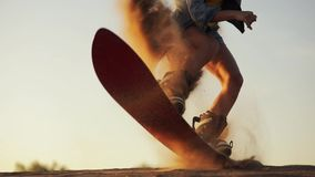 Detail a young beautiful girl hipster athlete in shorts tries doing tricks with a Board on sand dunes slow motion stock footage