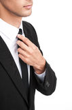 Detail of young businessman adjusting his necktie. Royalty Free Stock Photos
