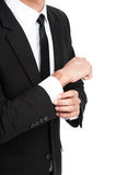 Detail of young businessman adjusting his sleeve. Royalty Free Stock Photos