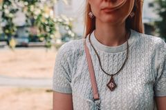 Detail of young cute woman wearing bijouterie on the street. Female fashion concept stock image