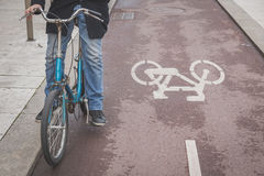 Detail of a young man posing with his bicyle. Detail of a young man posing with his bicycle in the city streets Stock Photography
