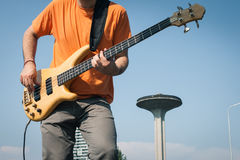 Detail of a young musician playing bass guitar. In suburbs Royalty Free Stock Photography