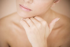 Detail of young woman's face, holding her hand to her chin Stock Photos