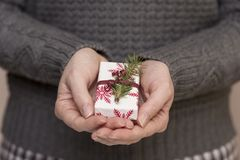 Christmas gift. Detail of a young woman`s hands holding a nicely wrapped present box Stock Photography