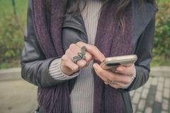 Detail of a young woman texting in the city streets Royalty Free Stock Photos