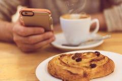 Detailbeeld van unrecognisable mens het drinken koffie en het houden van slimme telefoon terwijl het hebben van ontbijt in restau stock fotografie