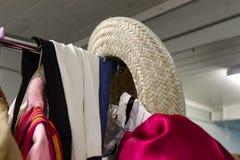 Detailclose-up van kledingsrek van kostuumscoulisse bij het theater met de hoed van de strocowboy het hangen op eind - selectieve stock foto