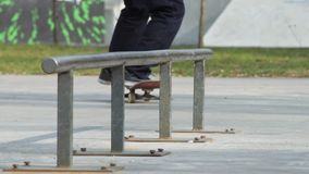 Skater make grind feeble 180 on rail in skatepark, close-up view in slowmotion. Detailed angle. Skateboarder make grind trick feeble 180 out - also feeble to stock video footage