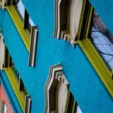 A detailed, angled look up at a colorful historic 1800s building. A beautiful old Italianate style building with restored lintels and windows. Blue brick, green royalty free stock photography