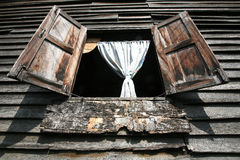 Detailed background: grunge wooden wall. And open window with curtain at traditional Thai house Stock Images