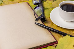 Detailed book, bright autumn leaves, a hot drink in a mug Royalty Free Stock Images
