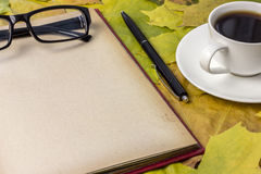 Detailed book, bright autumn leaves, a hot drink in a mug Royalty Free Stock Image