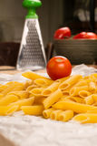 Detailed close up of a Italian pasta with a tomato and a kitchen utensils background Stock Photo