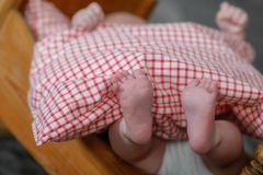 Detailed close up of newborn baby feet under checkered blanket stock images