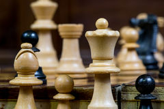 Detailed close up of white chess figures - white bishop, pawn and queen, black pawn Stock Image