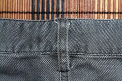 Detailed closeup of blank grungy denim. Vintage gray jeans with laces, good for background Stock Photo