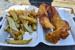 Detailed closeup of british fish and chips in polystyrene takeaway box. royalty free stock images