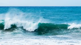 Detailed curling waves near the beach. Detailed curling waves with a lot of white foam in the wind near the beach. Puerto Plata, Dominican Republic stock photo