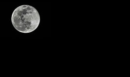 Detailed full moon on black background Stock Images