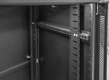 Interior view of a front vertical mounting post used to attach Networking and Server hardware, seen within a cabinet. Detailed image of a cabinet used to mount royalty free stock photos