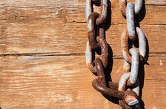 Wood board with iron chain link. Rusted chain hangin in front of a wooden background. Steel chain. Industrial detailed background. Detailed industrial background stock image