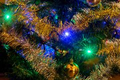 The detailed look at decorations on Christmas tree. The detailed look at Christmas decorations with lighting bulb on Christmas tree Stock Image