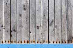 Detailed old wood planks with rusted screws texture. Detailed texture of wood planks with rusted screws and a blue rail at the bottom. Suitable for web and print Royalty Free Stock Photos