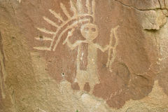 Detailed Petroglyph 2. Petroglyph in Northern New Mexico. Figure wearing feathered head dress with rattle and bow in hand Stock Photos