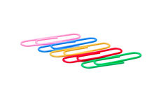 Detailed Photo of a Colorful Row of Paper Clips. Closeup view of a diagonal row of multicolored paper clips isolated on a white background Royalty Free Stock Images