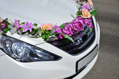 A detailed photo of the hood of the wedding car, decorated with many different flowers. The car is prepared for a wedding ceremon royalty free stock photo