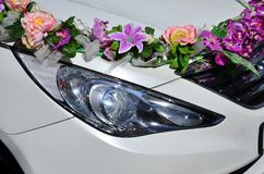A detailed photo of the hood of the wedding car, decorated with many different flowers. The car is prepared for a wedding ceremon. Y Stock Images