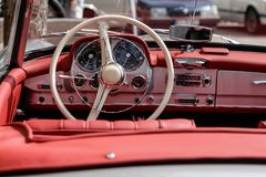 Interior of a classic oldtimer luxury sports car. Detailed photo of the interior dashboard, steering wheel and speedometer of a classic oldtimer sports car Stock Images