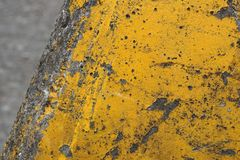 Yellow cracked paint on old concrete. A detailed photo of a old yellow cracked paint on old concrete royalty free stock photos