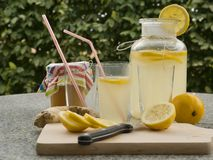Detailed Picture of all ingredients neccesary to cook a homemade lemonade consist from water, lemon, ginger and glass of honey. Pitcher, chopping board Stock Images