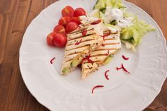 Detailed Picture of baked wraps, fachitas or burrito with fresh chili pieces, cherry tomatoes and fresh salad with cream Royalty Free Stock Photo