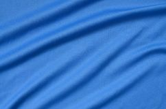 Detailed polyester blue fabric texture with many folds. Detailed polyester blue fabric texture with many long folds stock images