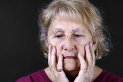Detailed portrait of a sad senior woman. Dramatic portrait of a sad, depressed or worried senior woman with hands in her face, studio shot over black background Stock Image