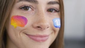 Detailed portrait of a young beautiful woman. Multicolor icon of social media painted on the girl`s face. Body art. Concept. Cute artwork on a humans body. Side stock footage