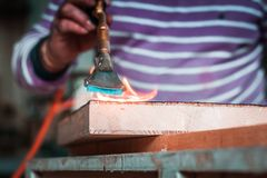 Expert carpenter burning a wood slab with a professional gas burner. Flames and smoke, fire and timber. Detailed shot of a professional carpenter, in his royalty free stock photos