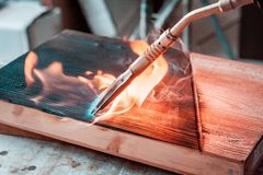 Expert carpenter burning a wood slab with a professional gas burner. Flames and smoke, fire and timber. Detailed shot of a professional carpenter, in his royalty free stock photography