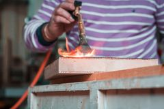 Expert carpenter burning a wood slab with a professional gas burner. Flames and smoke, fire and timber. Detailed shot of a professional carpenter, in his stock photos
