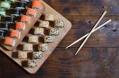 A detailed shot of a set of Japanese sushi rolls and a device for their use chopsticks, which are located on a wooden cutting b. Oard on a table in the kitchen Stock Photo
