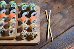 A detailed shot of a set of Japanese sushi rolls and a device for their use chopsticks, which are located on a wooden cutting b. Oard on a table in the kitchen Stock Image