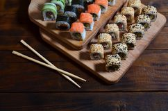 A detailed shot of a set of Japanese sushi rolls and a device for their use chopsticks, which are located on a wooden cutting b. Oard on a table in the kitchen Royalty Free Stock Image