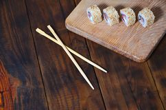 A detailed shot of a set of Japanese sushi rolls and a device for their use chopsticks, which are located on a wooden cutting b. Oard on a table in the kitchen Stock Photos