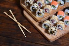 A detailed shot of a set of Japanese sushi rolls and a device for their use chopsticks, which are located on a wooden cutting boa. Rd on a table in the kitchen Stock Photography