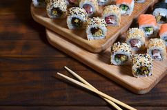 A detailed shot of a set of Japanese sushi rolls and a device for their use chopsticks, which are located on a wooden cutting boa. Rd on a table in the kitchen Royalty Free Stock Images
